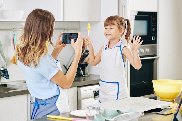 Молодая женщина фотографирует свою дочь или сестру с силиконовой щеткой на кухне, когда они вместе пекут