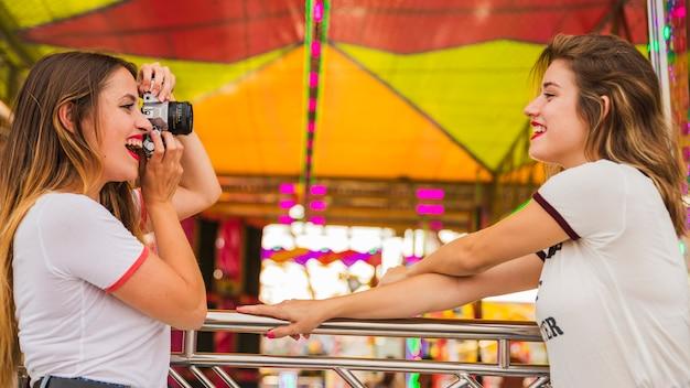 遊園地で彼女の笑顔の友人の写真を撮っている若い女性