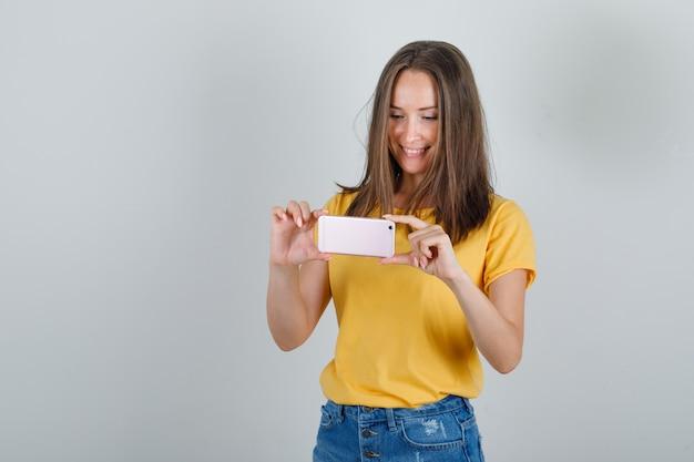 Tシャツ、ショートパンツ、嬉しそうに見える電話で写真を撮る若い女性