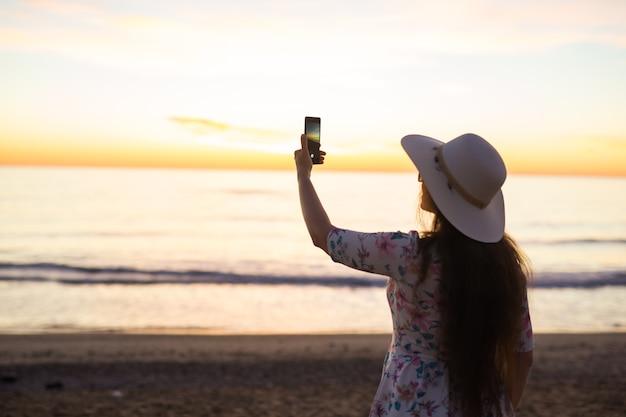 投稿用の携帯電話やスマートフォンのデジタルカメラで海と夕日の写真を撮る若い女性