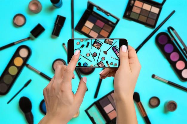 Молодая женщина фотографирует косметику с помощью цифрового фотоаппарата мобильного телефона или смартфона для публикации в интернете для продажи в интернете. интернет-бизнес концепция интернета вещей