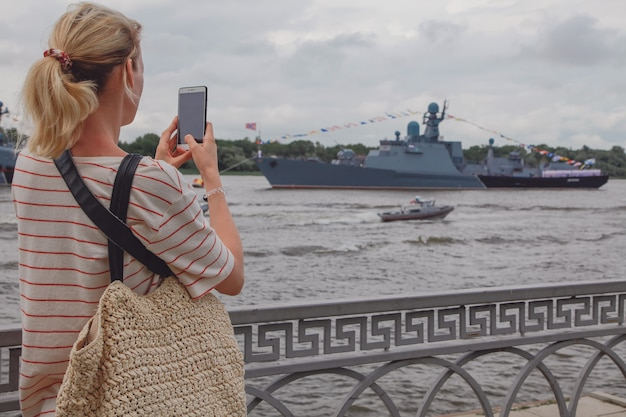 Young woman taking a photo of warships on the volga river in russia. russian warships in volga river in astrakhan in summer at cloudy day. russian military vessels.