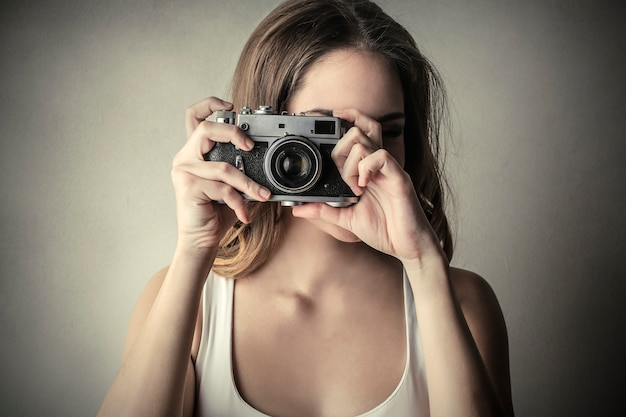 Young woman taking a photo with a camera