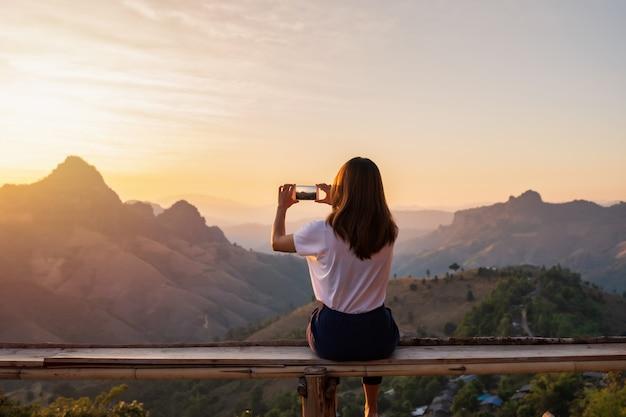 Молодая женщина с фото с смартфон на закате над горой
