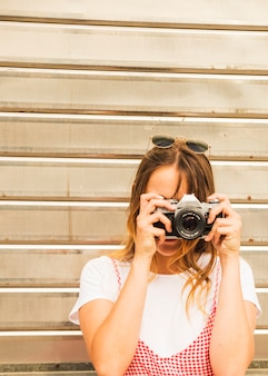 Young woman taking photograph with camera