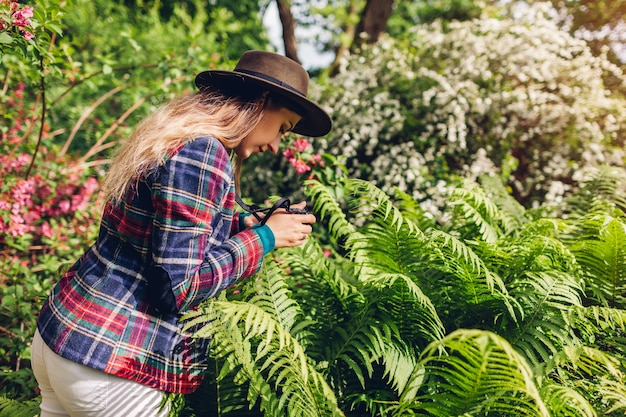 Young woman taking photographs on compact camera in summer garden. happy girl taking pictures of fern in park enjoying nature