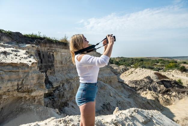 Young woman taking photos at sand rocks canyon, exploring nature, sunny weather