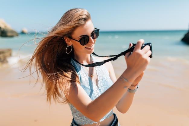 ビーチで写真カメラで写真を撮る若い女性
