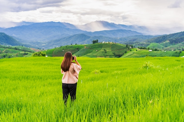 Young woman taking a picture of green rice terraces