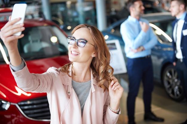 自動車販売店で写真を撮る若い女性