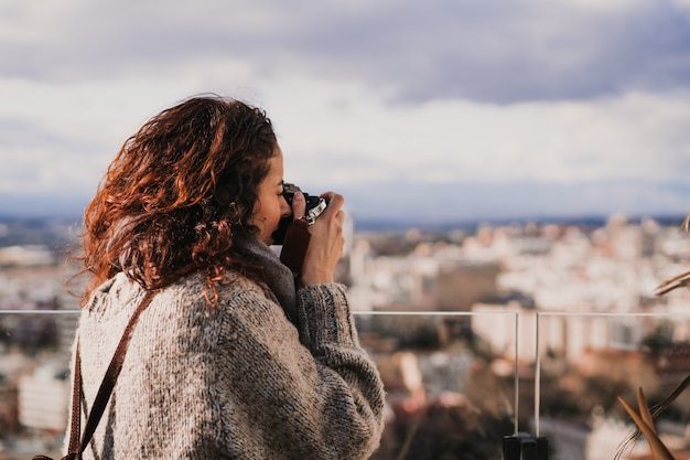 Young woman taking a picture of madrid city from a high building. travel and tourism concept