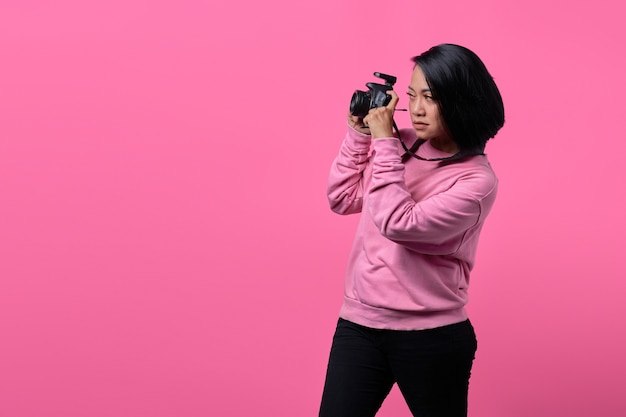 黒のプロのカメラで写真を撮る若い女性