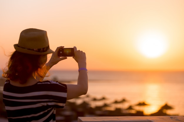 Young woman taking picture of sea sunrise