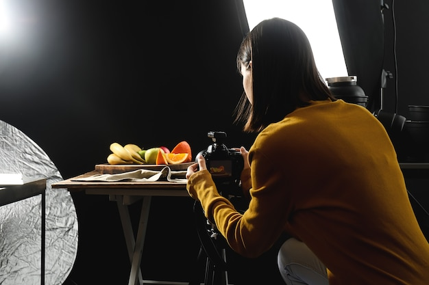 Young woman taking picture of tasty fruits in professional photo studio