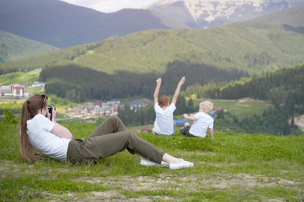 Young woman taking pictures of two young boys. back view. mountains