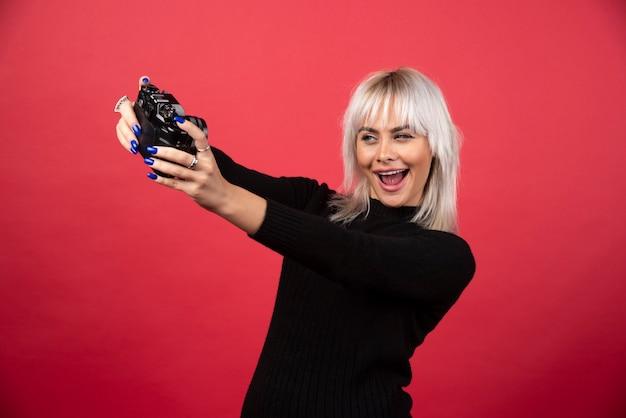 Молодая женщина фотографирует с камерой на красном фоне. фото высокого качества