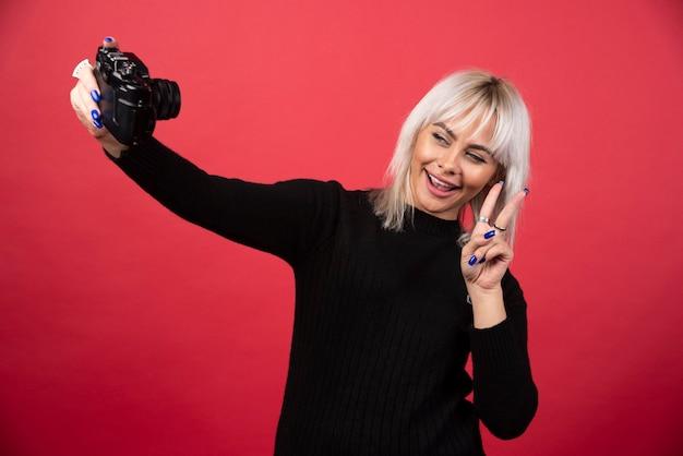 赤い背景の上のカメラで写真を撮る若い女性。高品質の写真