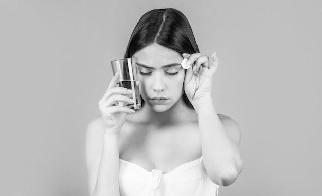 Молодая женщина принимает таблетки от головной боли. брюнетка принимает таблетку, запивая стаканом воды. черное и белое.