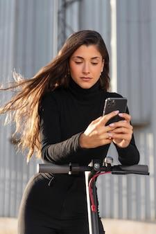 Giovane donna che fa un giro con uno scooter