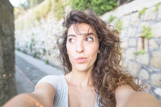 屋外でセルフをしている若い女性