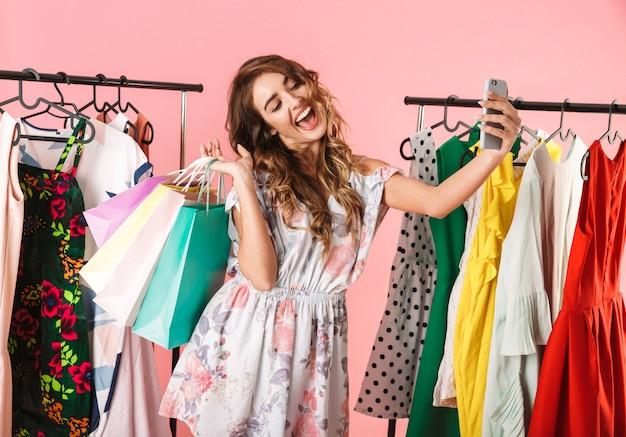 Молодая женщина делает селфи на смартфоне в магазине возле вешалки с красочными сумками, изолированными на розовом