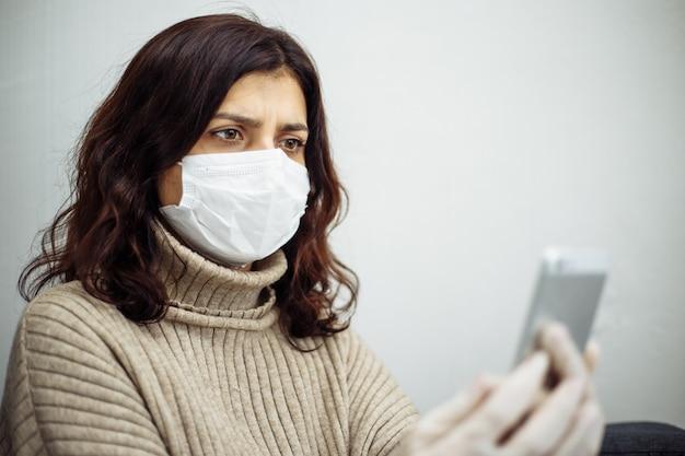 コロナウイルスパンデミックのため、自撮り写真を撮り、検疫中に自宅で仕事をしている若い女性。美しい少女は、医療用マスクと手袋を着用して家にいます。 covid-19エピデミックの概念。
