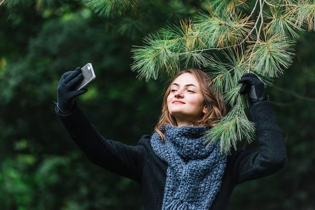 Giovane donna che cattura selfie su smartphone vicino ramoscello di conifere