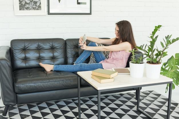 Молодая женщина, делающая селфи, сидя на диване у себя дома