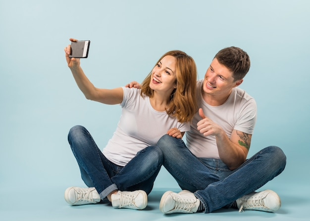 Young woman taking selfie with her boyfriend showing thumb up sign