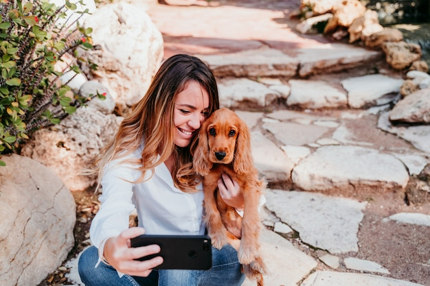Young woman taking a selfie with her cute puppy of cocker spaniel outdoors