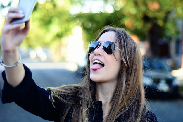 Young woman taking selfie with her smartphone.