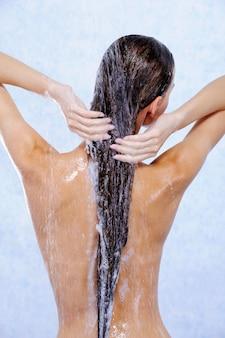シャワーを浴びて髪を洗う若い女性-背面図