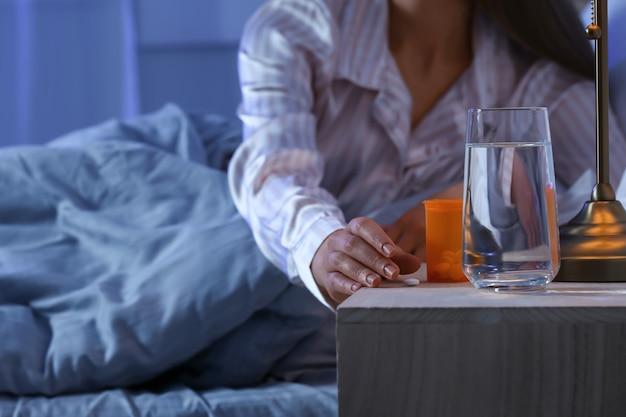 Молодая женщина принимает снотворное ночью