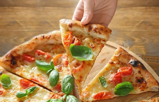 テーブルの上でおいしいピザマルゲリータのスライスを取る若い女性