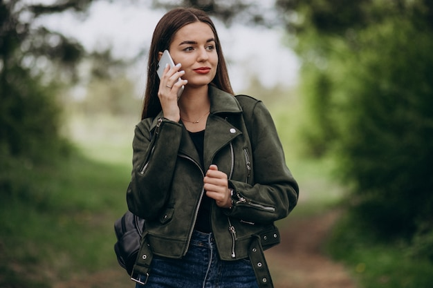 Young woman talkimng on the phone in park