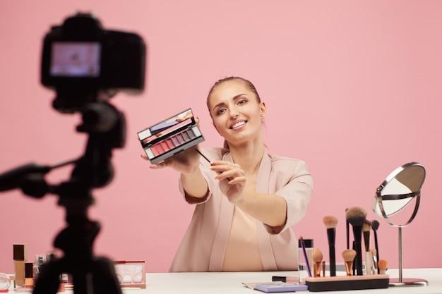 Молодая женщина рассказывает о декоративной косметике и показывает в камеру тени для век, делая косметический контент