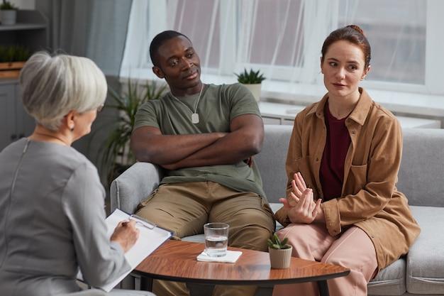 相談中に夫と一緒にソファに座って心理学者に自分の問題について話している若い女性