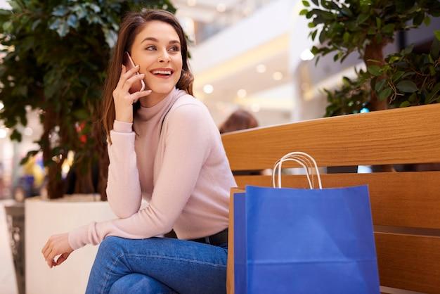 큰 쇼핑 후 휴대 전화로 얘기 하는 젊은 여자