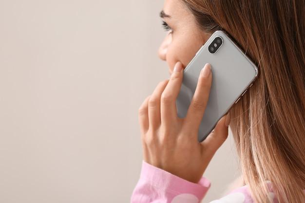 Молодая женщина разговаривает по мобильному телефону в спальне