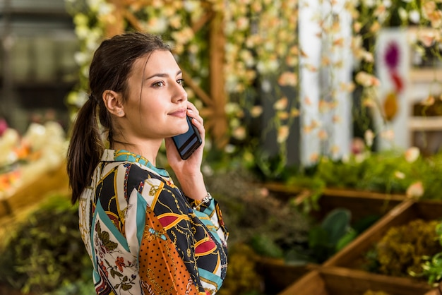 Young woman talking by phone in green house