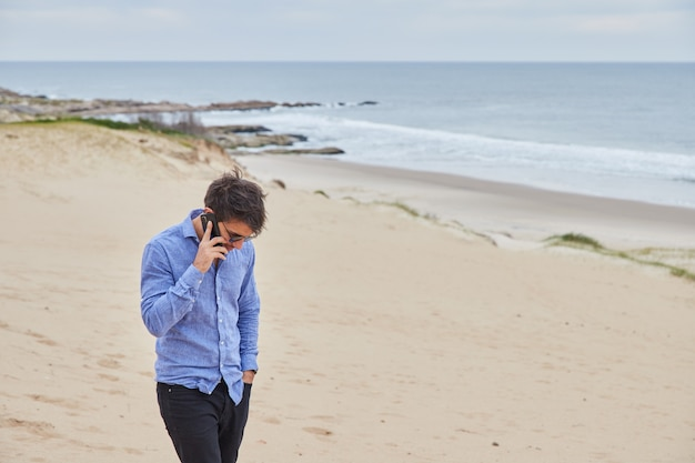 Young woman talking on cell phone on the beach while wearing sunglasses and light blue shirt. he looks down worriedly, while in the background you can see the sand and the ocean.