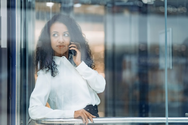 Young woman talking on her smartphone and looking through the glass of the elevator
