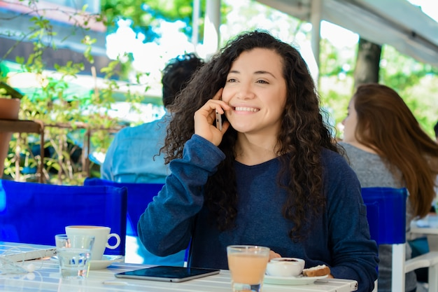 Young woman talking on mobile phone at coffee shop