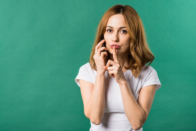 Young woman talking on mobile phone making silence gesture against green background