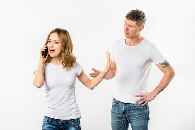 Young woman talking on mobile phone showing stop gesture to her boyfriend