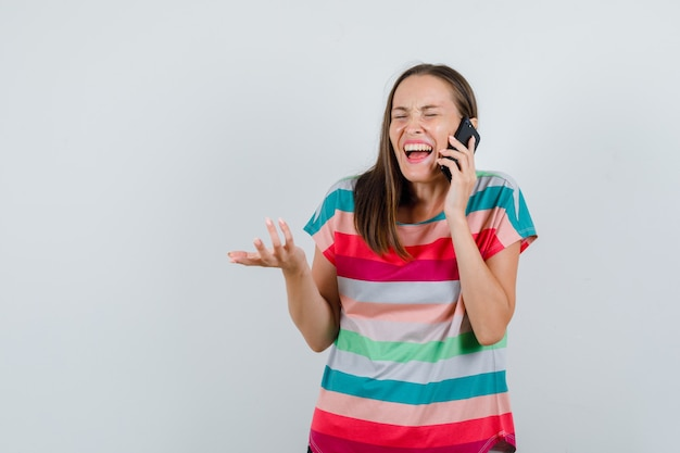 Young woman talking on mobile phone in t-shirt and looking happy , front view.