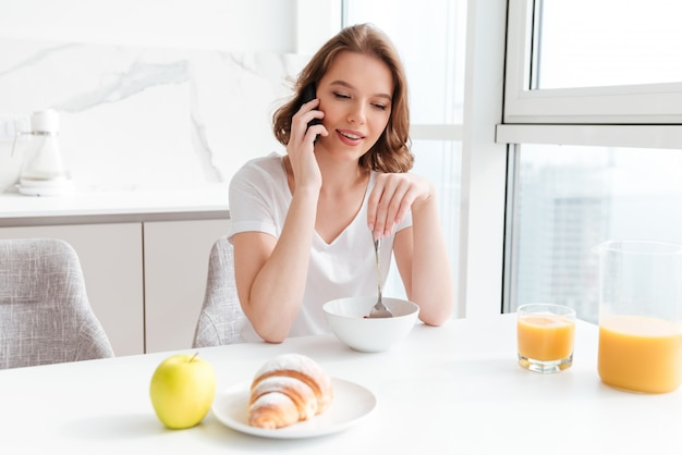 Young woman talking on mobile phone while having breakfast at the kitchen table