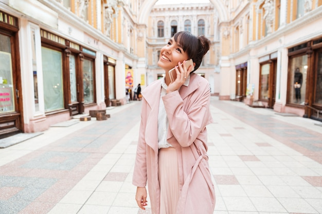 Giovane donna che parla sul telefono cellulare mentre levandosi in piedi alla via