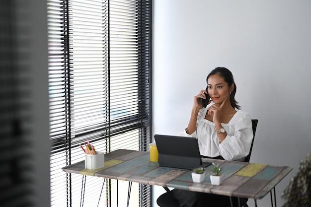 Молодая женщина разговаривает по мобильному телефону в офисе