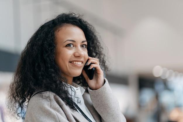 ショッピングセンターのカフェテリアでスマートフォンで話している若い女性